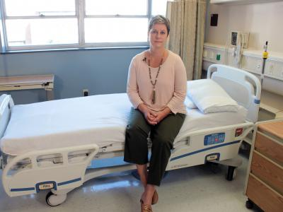 Aime Kunes sits on a hospital bed in the CCTS Inpatient Research Unit