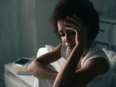 Early adult, thin Black woman with natural hair sitting in bed and holding her head with one hand.