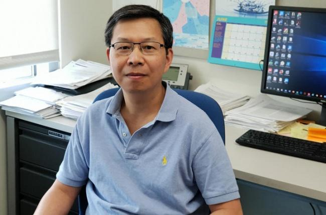 Dr. Dr. Qing-Bai She sits facing the camera with his back to his desk and computer screen. He is wearing a pale blue polo shirt and glasses.