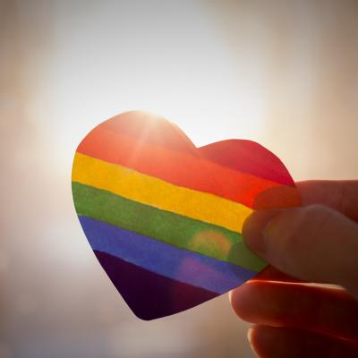 A heart in rainbow colors being held up to the sunlight.