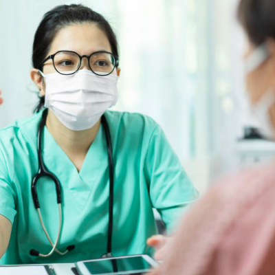 Health care provider at desk in mask talking to patient in mask.
