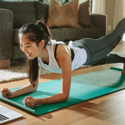 A female on yoga mat interacting with a laptop